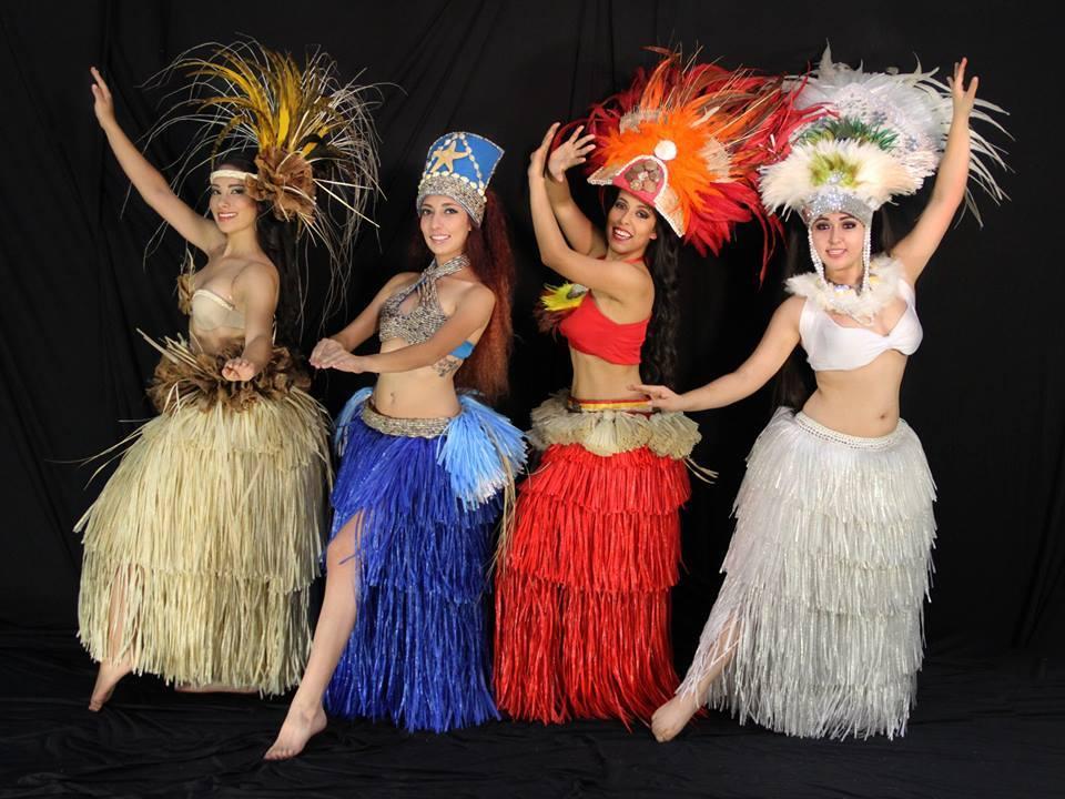 maestras de danza tahitiana con su atuendo típico posando para la cámara